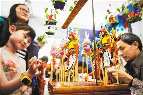 4月18日,在解放碑步行街,剪纸、面塑、糖画等非遗传承人在现场创作。见习记者 苏思 摄