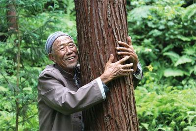 刘安国老书记像爱自己的孩子一样拥抱着这些当年自己和乡亲们亲手种下的树木