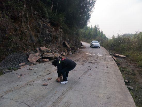 人保查勘员在清理乡村公路上地震引发的落石