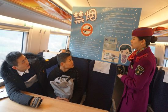 图为列车长将列车上吸烟会造成危害向旅客宣传
