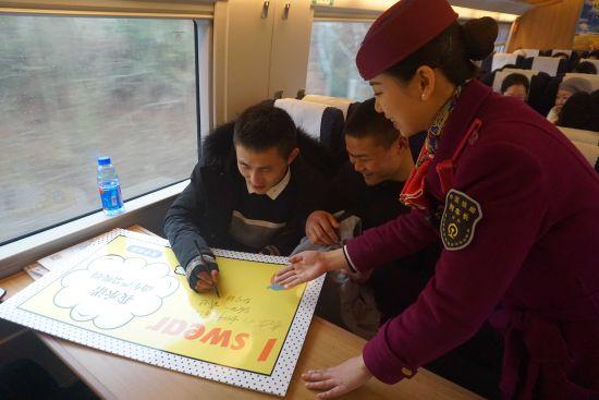 图为列车长邀请旅客签字承诺禁止吸烟