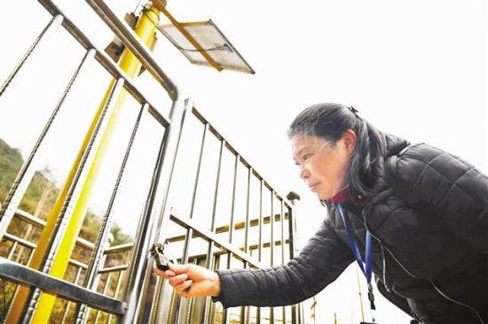 2月16日,渝北区木耳镇金刚村大柏树区域,地灾监测巡防员王德芬正在检查地质监测设备。记者 谢智强 摄