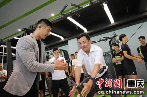 图为 邢傲伟指导体育学院院长唐建忠使用健身设备。 陈超 摄