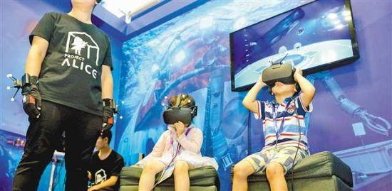 """6月22日,在南坪国际会展中心,小朋友在深海虚拟现实技术联合实验室体验随""""深海勇士""""号载人潜水艇""""下潜""""到4500米。 (图片均由记者张锦辉、罗斌摄)"""