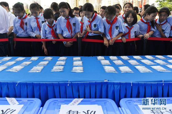 """6月26日,国际禁毒日,重庆在川剧院广场举行""""感恩生命,健康生活""""主题宣传活动,小学生参观现场展示的毒品。新华网 李相博 摄"""