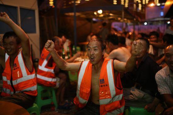 图为中建七局西南公司环球欢乐世界项目的农民工在生活区观看2018年俄罗斯世界杯。 中建七局西南公司供图