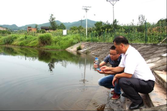 圖為福果鎮鎮干部在塘里提取水樣。 重慶銅梁區委宣傳部新聞辦公室供圖