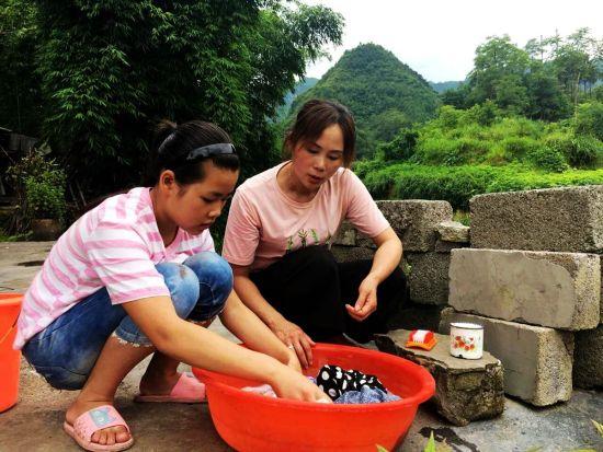 爱心妈妈陈玮手把手教留守孩子学习洗自己的衣服(姚华顺 摄)