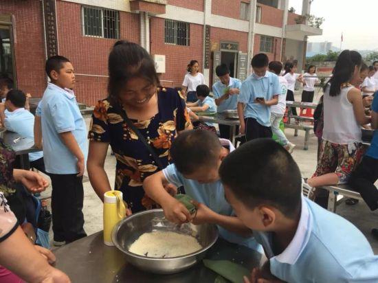 家长与孩子共享包粽子的快乐(姚华顺 摄)
