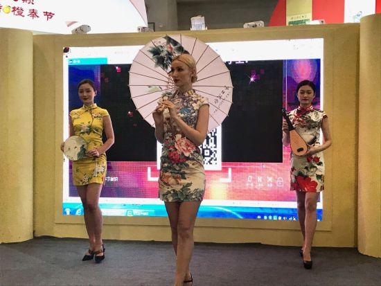 图为三位穿旗袍服饰的美少女在奉节展馆轻盈地舞蹈