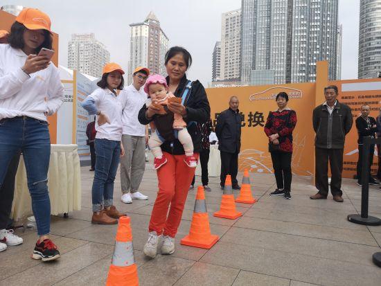 """图为市民参与小游戏,体验""""开车看一眼手机等于盲开50米""""。摄影 刘贤"""