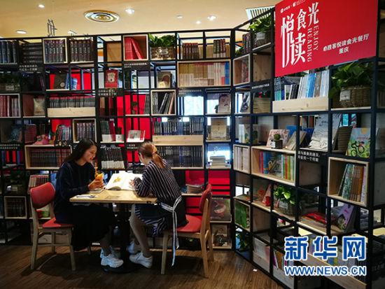 图为两位市民在餐厅内边吃美食边翻阅图书。新华网发(重庆出版集团供图)