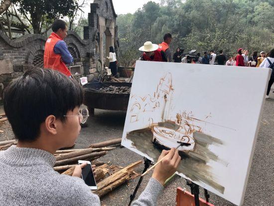图为一同学支起了画架,调好颜色,用画笔记录着现场。张翼飞 图