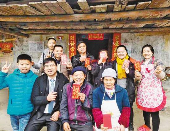 2月4日,游四海(前排左二)与收到慰问金的贫困家庭合影。(受访者供图)