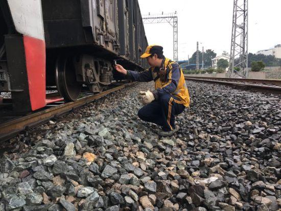 图为 铁路职工宋亮在轨道上进行摘车作业 万州火车站供图