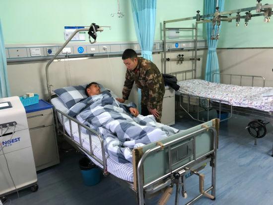 图为张伟波去医院看望被救伤者。重庆武警供图