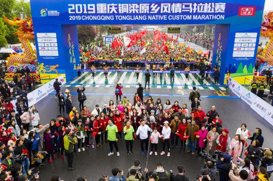 """图为 2019重庆铜梁原乡风情马拉松比赛现场""""快闪""""合唱""""我和我的祖国"""""""