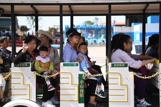 图1为小朋友们在家人陪伴下体验小火车。(陈超 摄)