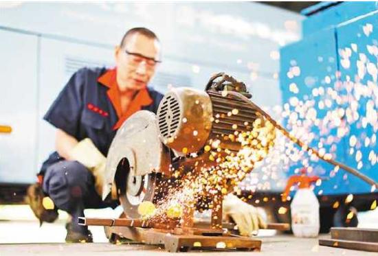 """5月1日,重庆西部公共交通有限公司梨树湾保修厂,工人正在加工零件。该厂""""五一""""期间每天都有350余名工人坚守岗位,确保城市公交车辆安全运行。通讯员 孙凯芳 摄"""