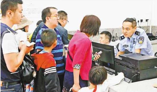5月2日中午,渝中区朝天门,重庆市公安局水上分局朝天门派出所民警正为游客们办理临时身份证。特约摄影 钟志兵