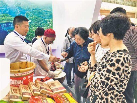 在重庆展区,工作人员给顾客讲述合川桃片的历史