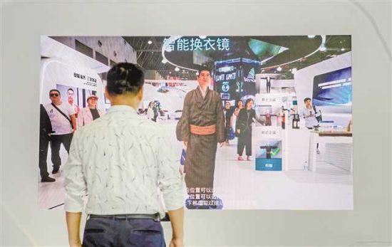 五月十七日,在西洽会保税港区展台,观展者通过智能换衣镜体验一秒换古装。