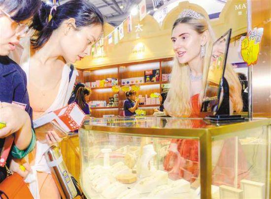 """5月17日,在西洽会""""一带一路""""(重庆)智能体验馆,来自捷克的工作人员正在介绍其带来的水晶饰品。"""