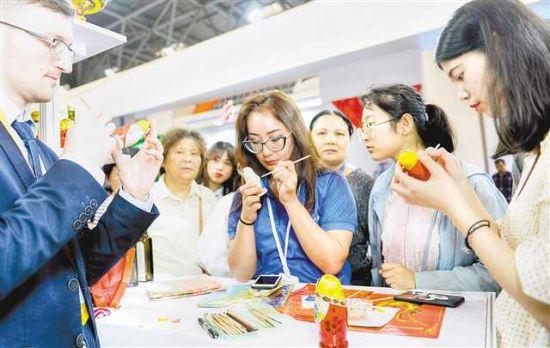 五月十七日,在西洽会国际馆俄罗斯展台,观展者和工作人员现场为套娃着色。
