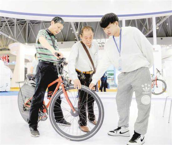 五月十七日,在西洽会江津展台,一款太阳能电动智能助力自行车样车引来观展者关注。