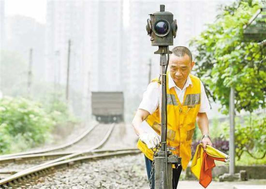 59岁的重庆南站调车区长王玉华在重庆南站驼峰最后一次调车作业中,人工进行手扳道岔作业(5月15日 刘潺 摄)