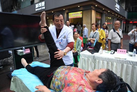 图为重庆汇康医院疼痛科吴士明医生为民众义诊。陈超 摄