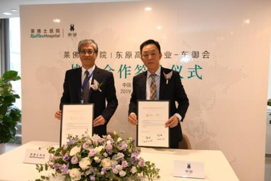 图为莱佛士医院(重庆)副院长兼总裁刘广洪教授(左)与东原物业集团总经理范东先生(右)签署合作备忘。 邓小军 摄