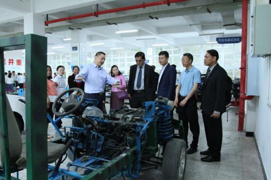 图为 秦小滨校长陪同泰国客人参观实训基地。校方供图