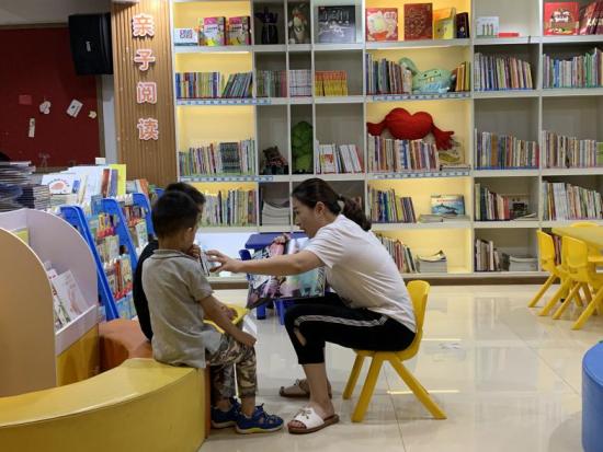 圖為 館內工作人員為社區小朋友講故事。(李定明 攝)