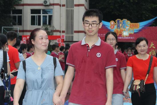 圖為家長和孩子一起跨過畢業門。楊鮮 攝