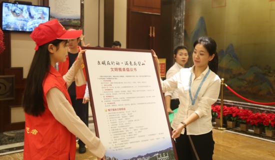 志愿者进酒店宣传文明用餐知识。