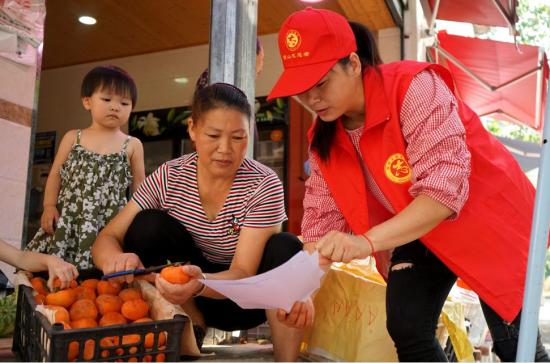 志愿者为摊贩宣传环保知识。