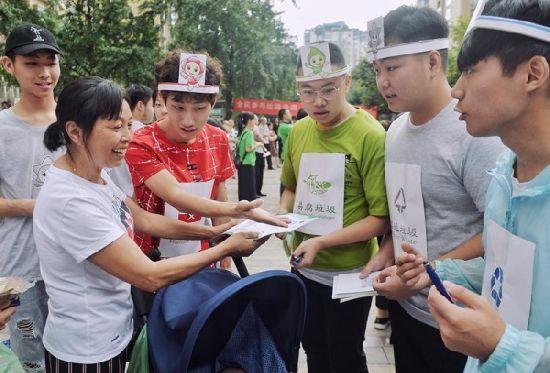 图为 大学生向市民宣传讲解垃圾分类知识。(彭利军 摄)