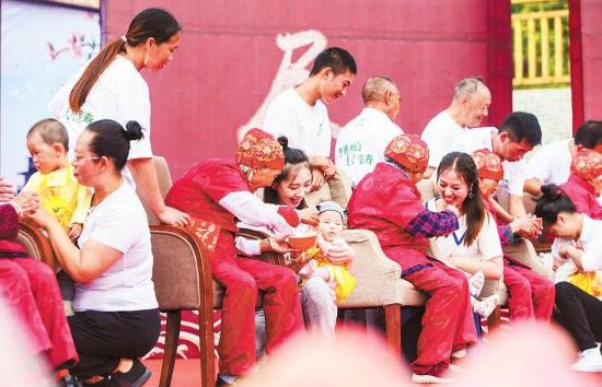 """7月13日,綦江区横山镇举行""""赶寿节"""",高寿老人为宝宝们""""开荤""""送福,寓意健康幸福,平安美满。 记者 万难 摄"""