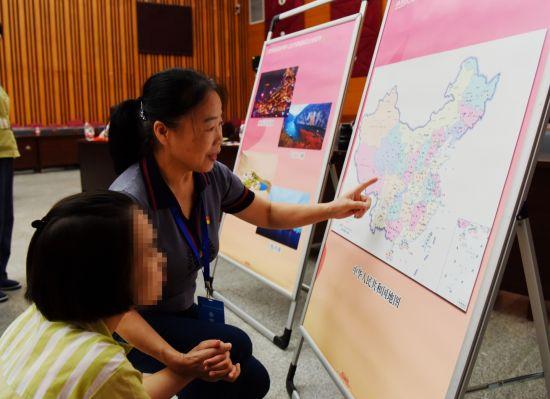 """8月9日,""""爱心妈妈""""余晓丽正在引导结对孩子在地图上查找她所喜爱的景点。"""