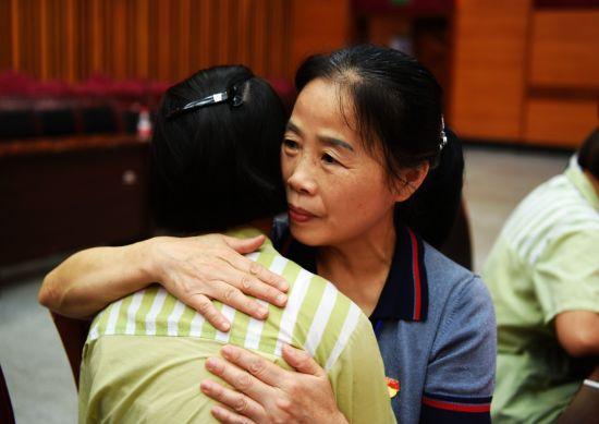 """8月9日,""""爱心妈妈""""余晓丽与她的结对孩子深情拥抱。"""