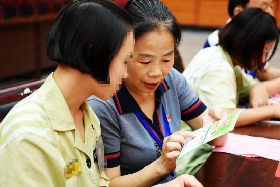 """8月9日,""""爱心妈妈""""余晓丽正在指导孩子填写""""爱心妈妈""""联系卡。"""