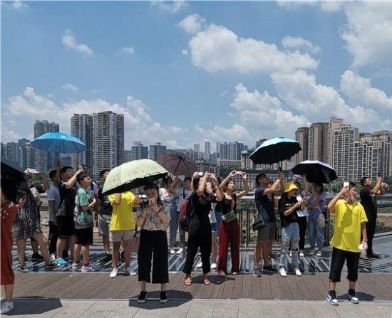 下午1时20分,艳阳高照,却照不散李子坝站下边的人群。