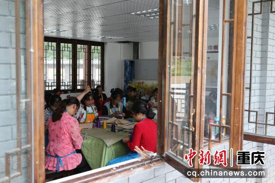 村民们在脱贫工坊中集中培训制作。