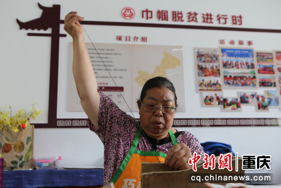 坪坝村65岁的残疾村民胡先祥在缝制手工产品。