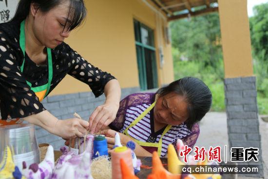 建峰村的建卡残疾村民张玉芳(左)到华溪村建卡村民谭明兰家中传授制作技术
