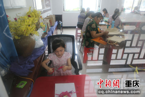 坪坝村的4岁小朋友余思怡陪着妈妈一起到工坊上班。