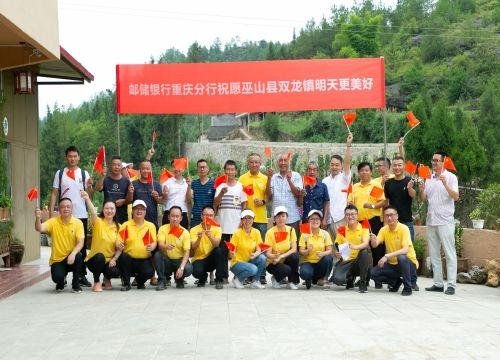 扶贫慰问工作组、巫山县双龙镇政府有关领导以及数位村民共同合影 邮储银行重庆分行供图