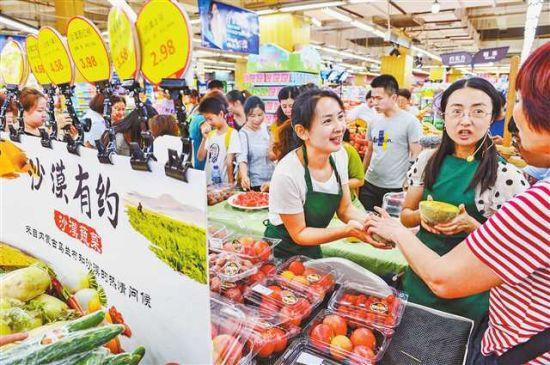 八月十四日,两江新区金渝大道新世纪超市,重庆交通大学的王敏博士(右二)正在为市民介绍产自沙漠的蔬菜。记者 万难 摄