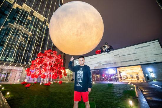 图为艺术家黄玉龙与月亮装置合影。重庆IFS供图